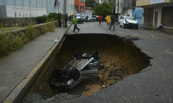 México: Auto queda dentro de un socavón originado por fuertes lluvias - Noticias de acapulco